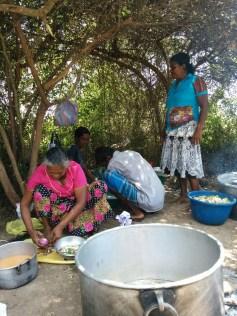 Villagers prepare meals in makeshift kitchen