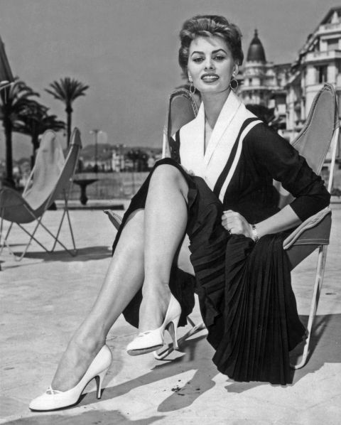 Sophia Loren lounges beachside in Cannes wearing an appropriately nautical-themed dress and perfect little white pumps.