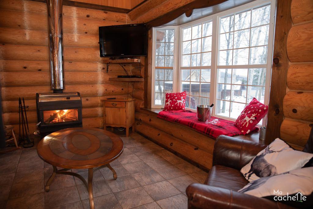 Petit Domaine forêt d'eau - Chalet bois rond à louer au Lac Simon - Salon avec foyer au bois