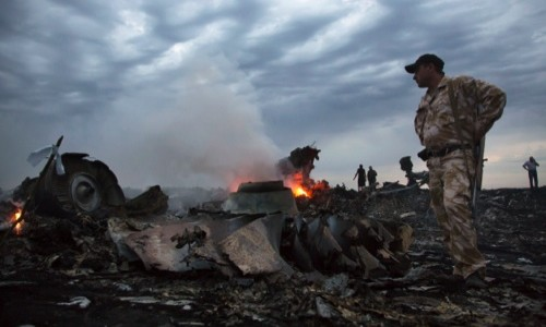People walk amongst the debris, at the crash site of a passenger plane near the village of Hrabove