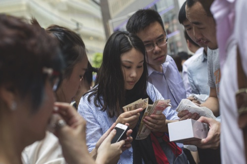 A woman counts Hong Kong dollar banknotes as people resell Apple iPhones across from the company's Causeway Bay store during the sales launch of the iPhone 6 and iPhone 6 Plus in Hong Kong, China