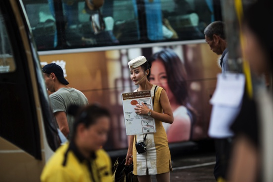An employee directs passengers to board a shuttle bus for Galaxy Macau casino resort
