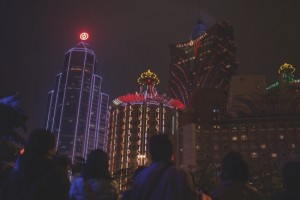Pedestrians walk in front of the Bank of China building, left, and the Casino Grand Lisboa in Macau