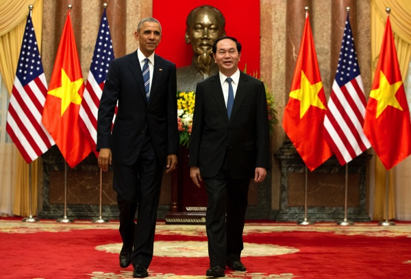 Barack Obama (left), and Vietnamese President Tran Dai Quang walk to a meeting after shaking hands at the Presidential Palace in Hanoi