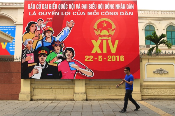 A man walks pass a billboard of Vietnam's Parliamentary Election in Hanoi