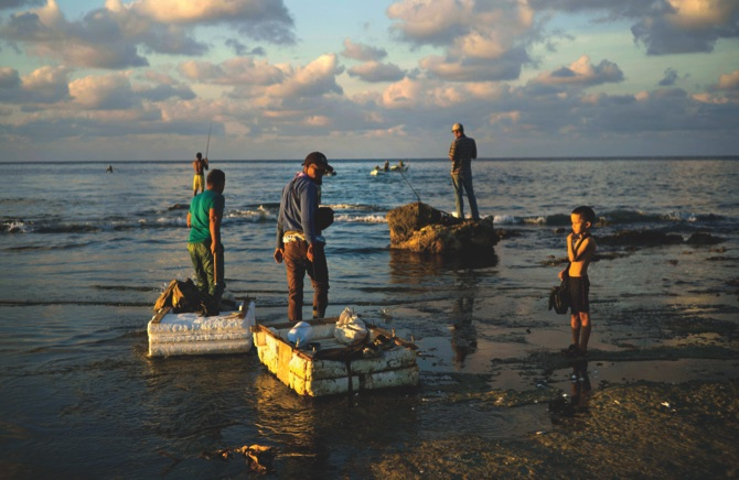 Young fishermen pull their rafts made out of foam as they head to sea from Chivo Beach