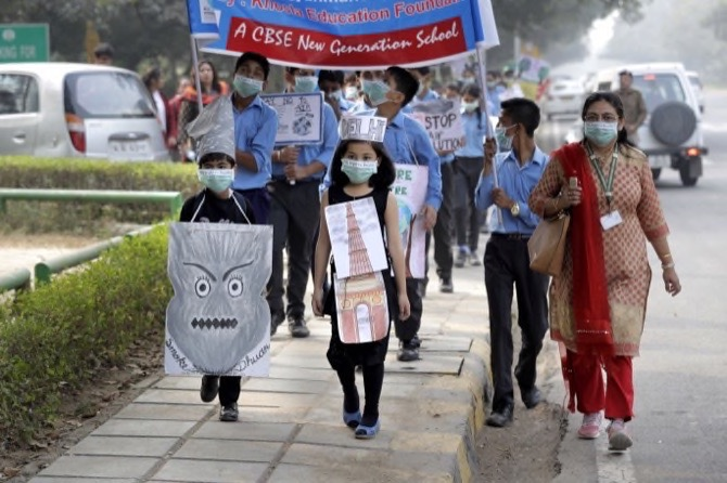 School children holding banners march to express their distress on the alarming levels of pollution in the city
