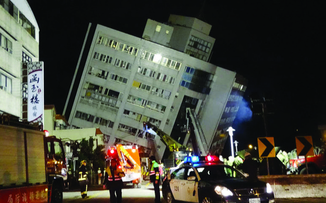 Rescuers are seen entering a building that collapsed onto its side from an early morning 6.4 magnitude earthquake in Hualien County eastern Taiwan