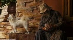 Ένας ηλικιωμένος μοναχός μαζί με τον πιστό του σύντροφο κάθεται στην είσοδο της μονής Δοχειαρίου