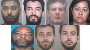 Seven store employees are accused of teaming up in an estimated half-million dollars theft scheme, police said