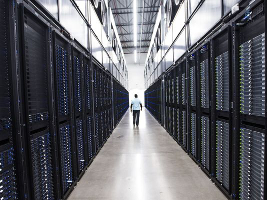 The senior site operations manager at the Apple Data Center in Mesa makes his way past dozens of servers, on Aug. 14, 2018. (Photo: Tom Tingle/The Republic)