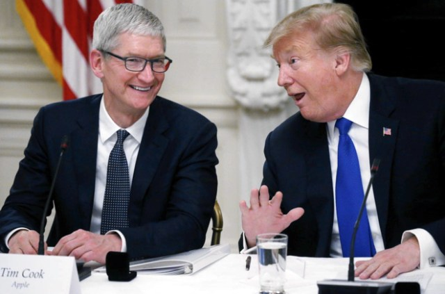 Apple CEO Tim Cook laughs with U.S. President Donald Trump as the news media leave the room after the two men spoke while participating in an American Workforce Policy Advisory Board meeting in the White House State Dining Room in Washington, U.S., March 6, 2019. (photo: Reuters/Leah Millis)
