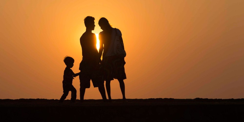Parents of today's world have many concerns when it comes to raising their children, most of which are driven by fear – creating what many have come to know as the helicopter parent. Pictured is parents with their child in a sunset.