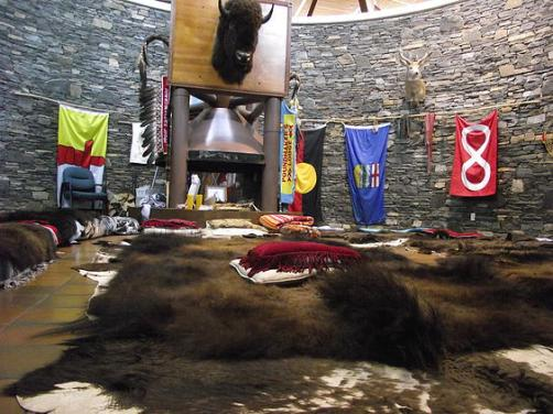 A red Metis flag hangs from the wall of a meeting area of the Poundmaker's Lodge.