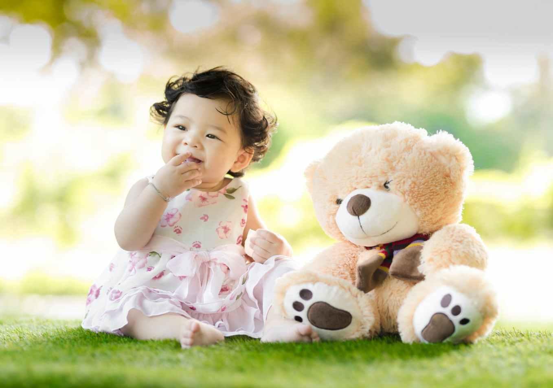 baby sitting on green grass beside bear plush toy at daytime