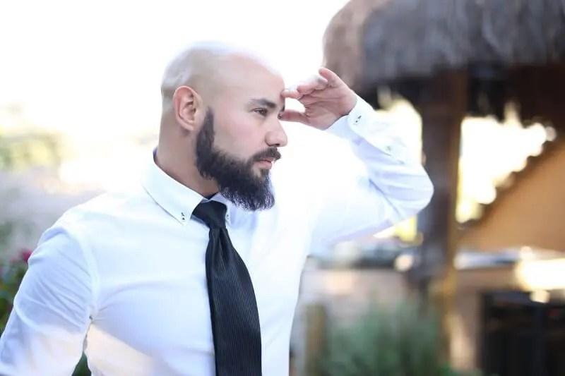 遠くを見る髭のある坊主の男性