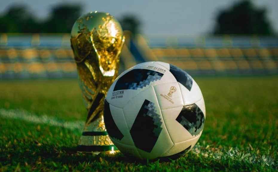 Na imagem bola de futebol ao lado do troféu Copa do mundo