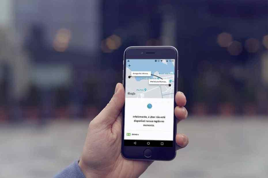 Mão segurando um celular com o app da Uber aberto e a mensagem de ela não está presente no local.