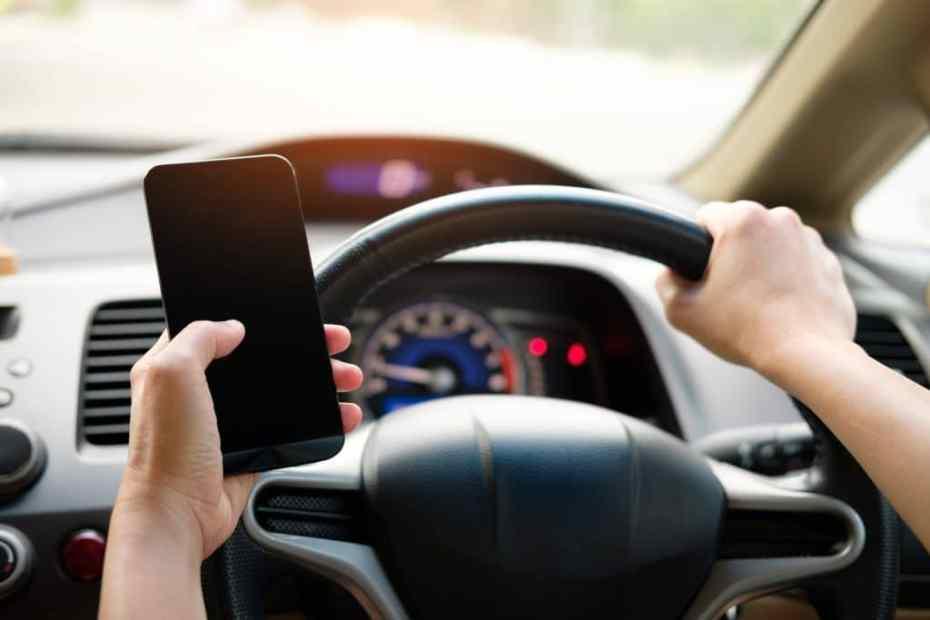 Na imagem, motorista está com a mão direita no valor e a esquerda segurando o telefone