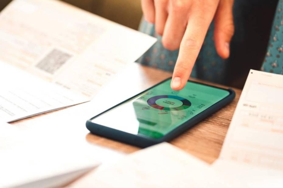 Celular sobre uma mesa, com uma pessoa tocando a tela com o dedo indicador.