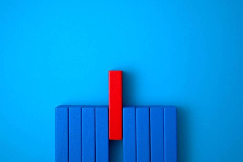 Peças de dominó azul com uma outra peça vermelha em destaque.