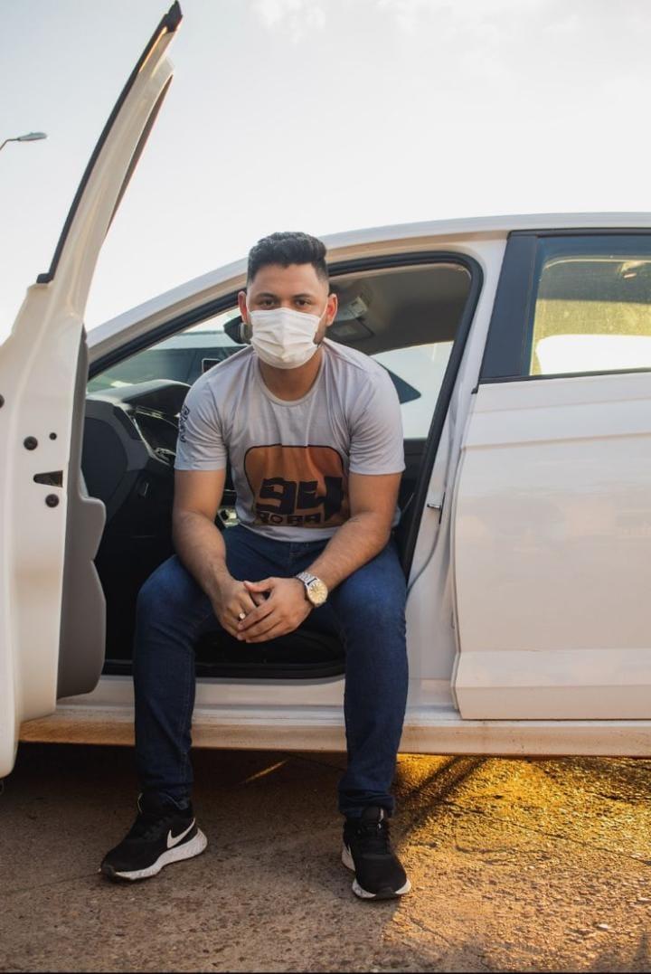 Fábio sentado no banco do motorista de um carro com a camiseta do Bora 94.