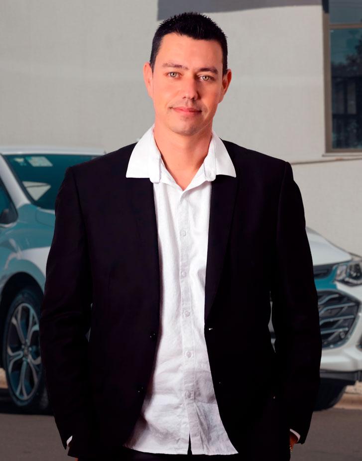 Angelo, co-fundador do aplicativo de transporte Chofer 46, parado em frente a um carro