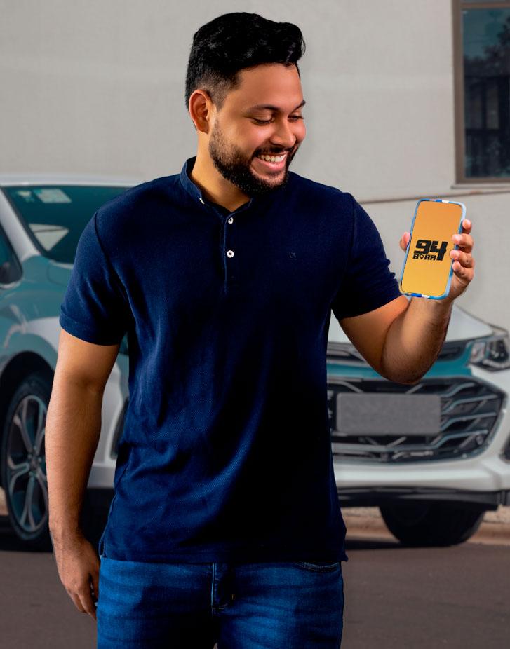 Fábio, dono da Bora 94, sorrindo e segurando um celular escrito Bora 94 com um carro ao fundo.