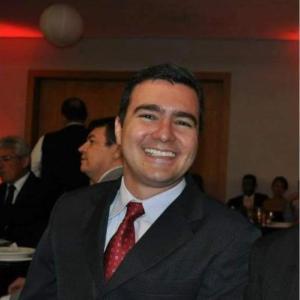 Chálaco, dono da maior franquia da Moovecar, sorrindo de terno e gravata vermelha.