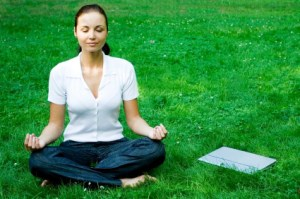 Young Woman Meditating on the grass