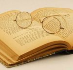 An old book lying open with round eyeglasses lying on top.