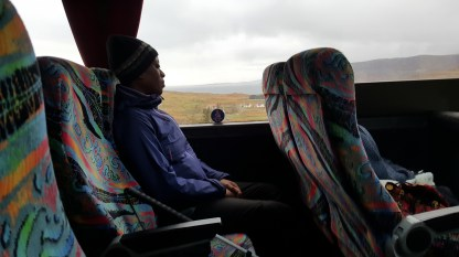A woman travelling by coach leans her head against the window through which hills and a bay of water are visible.