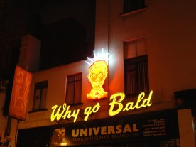 A neon sign with a full-haired man's head and the words Why go Bald?