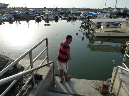 A young boy fishes in a port of small boats
