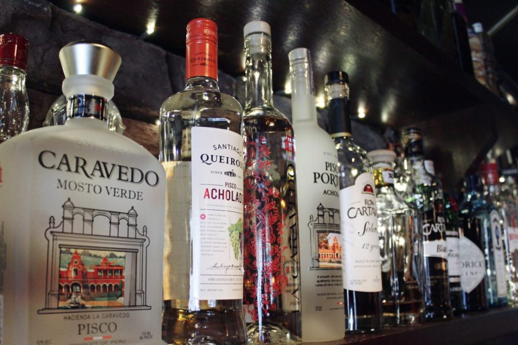 Pisco bottles on bar with twinkle lights behind them