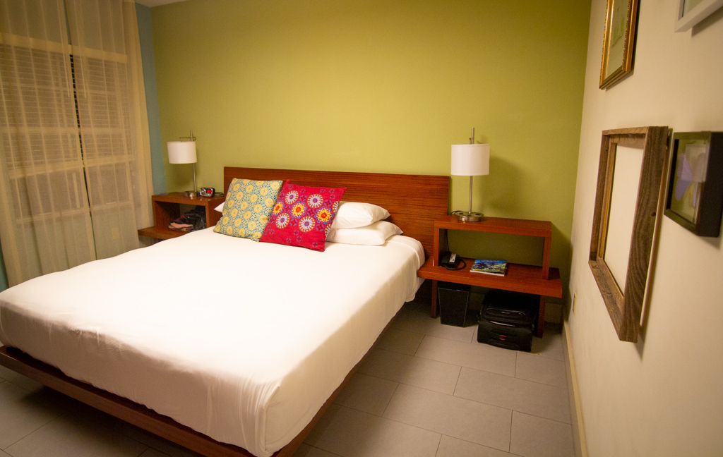 Bed with white cover and green wall, Miami