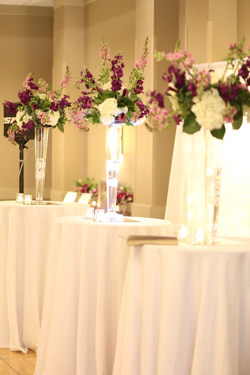 The cocktail tables.  Backdrop with light curtain. Eiffel vases with tall floral arrangements.