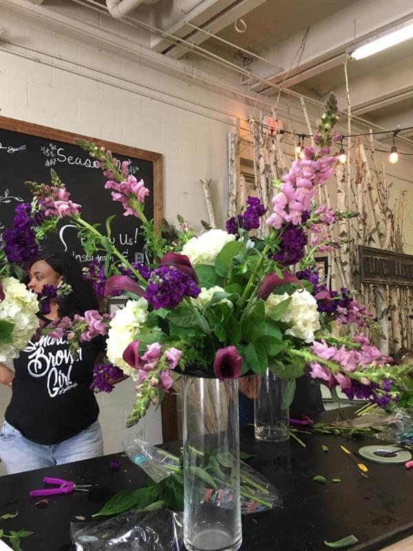Clear vase with pink snapdragons, white hydrangeas, purple stock, blue delphinium, purple calla lilies, italian ruscus, oasis foam.