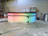 Illuminated Modern Reception Desk in Corian with Multi-colored LEDs at the glue up stage for Sub Zero Wolf
