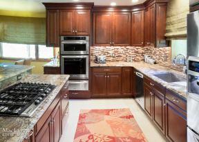 Warm Neptune Bordeaux Granite Kitchen with dark Cherry Cabinetry