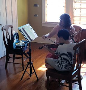 A young student learning violin from Ms. Patty Baser, the violin instructor at Greenwood School of Music.
