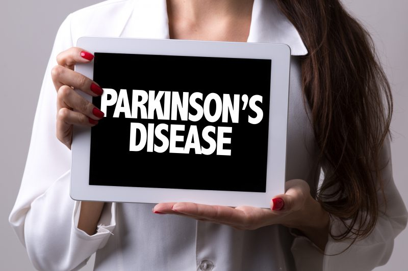 Female doctor holding a tablet with the text: Parkinsons Disease