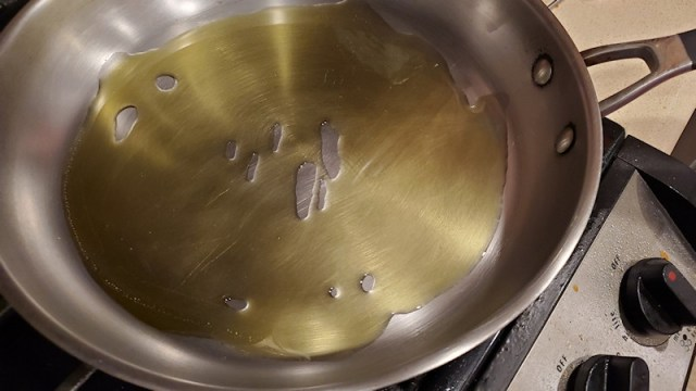 Olive oil heating up in a pan