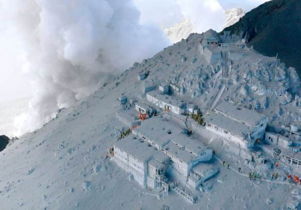 JSDF soldiers and firefighters conduct rescue operations at mountain lodges, covered with volcanic ash as volcanic smoke rises near the peak of Mt. Ontake, which straddles Nagano and Gifu prefectures