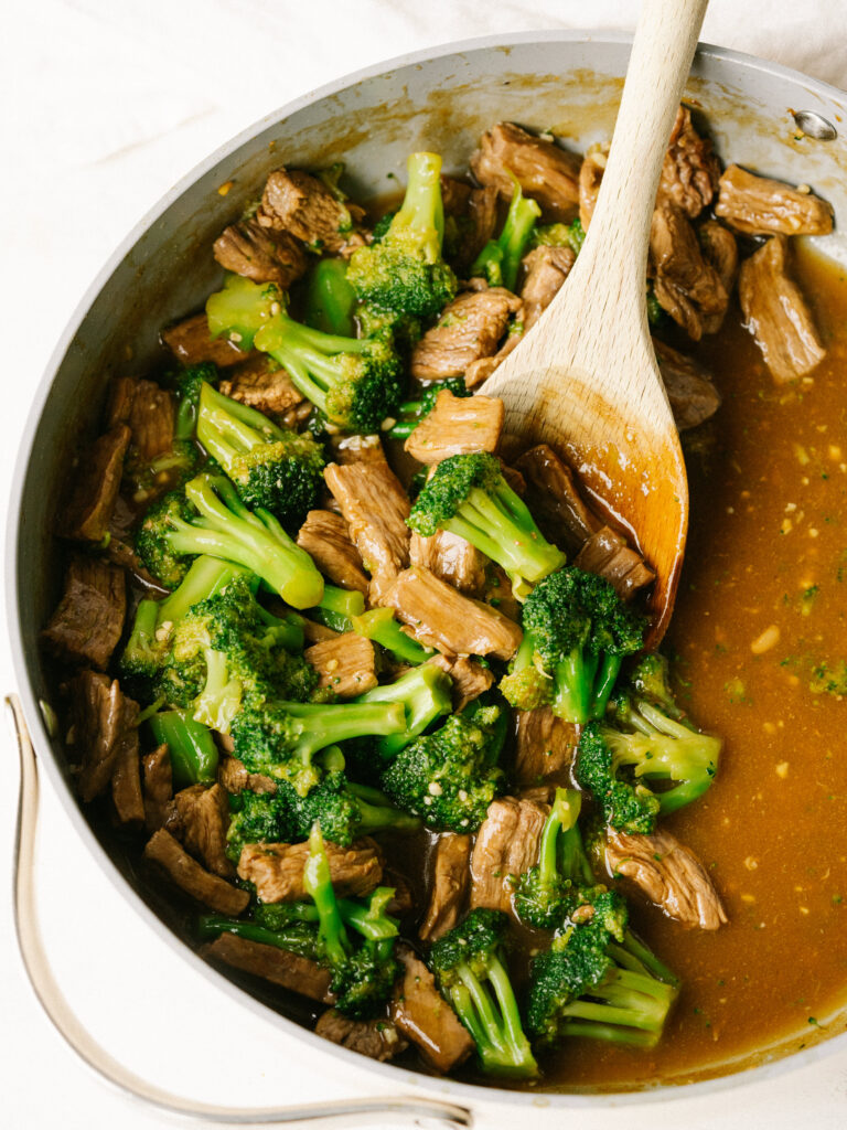 Above view of easy beef and broccoli recipe in a pan with a wooden spoon