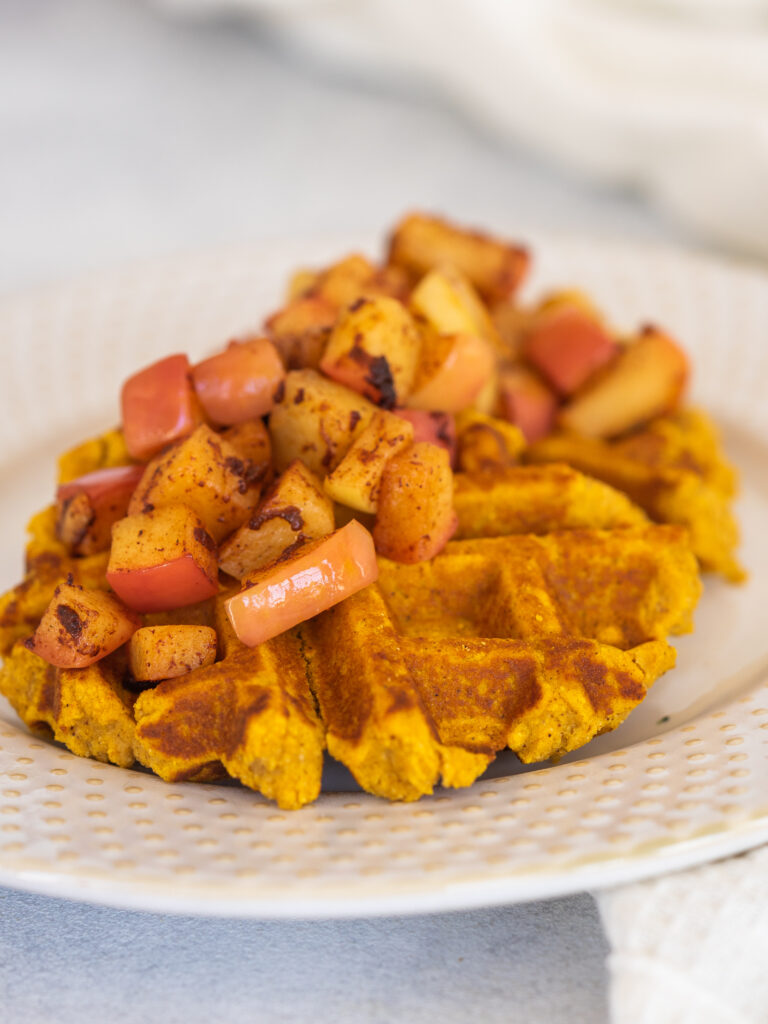 pumpkin spice waffles on a plate with cinnamon apples