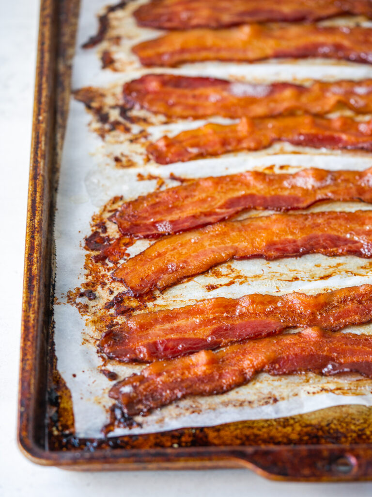 Three quarter view of crispy bacon on a baking sheet
