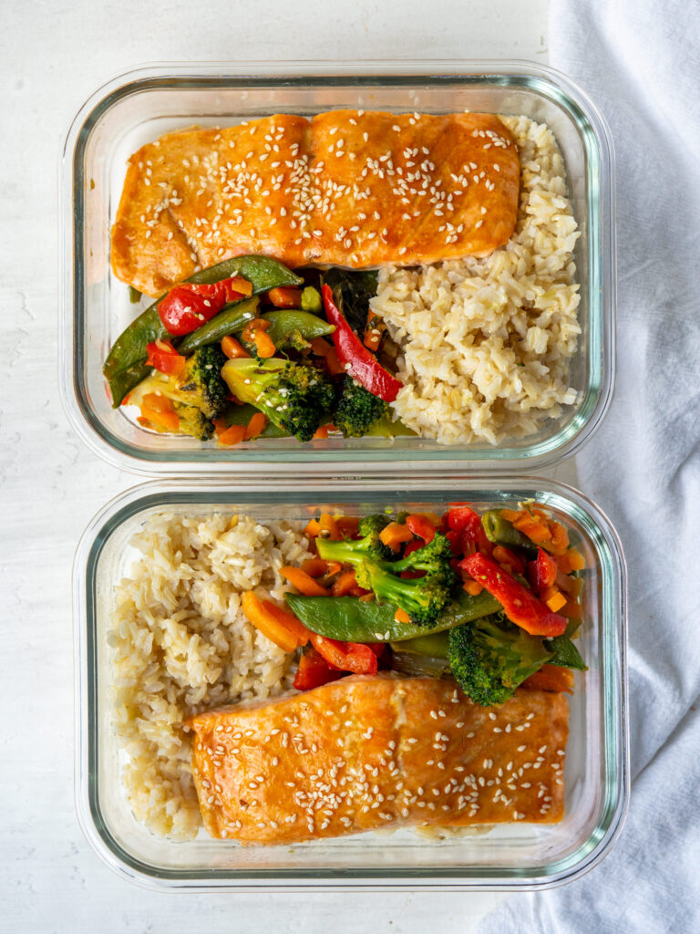sheet pan salmon dinner with rice in meal prep containers