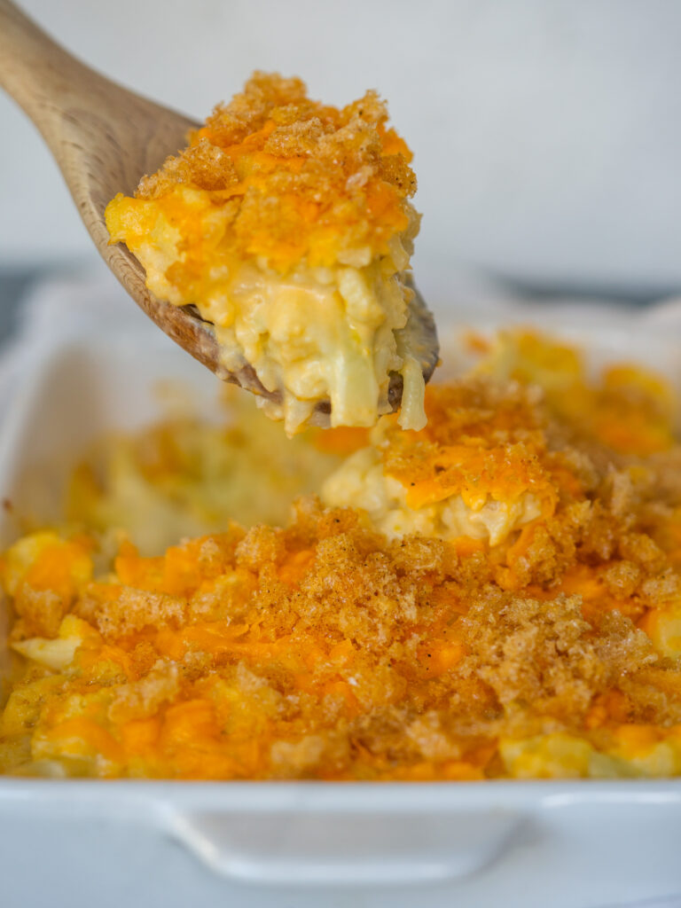 Side view of a wooden spoon scooping out a bite of baked cauliflower mac and cheese