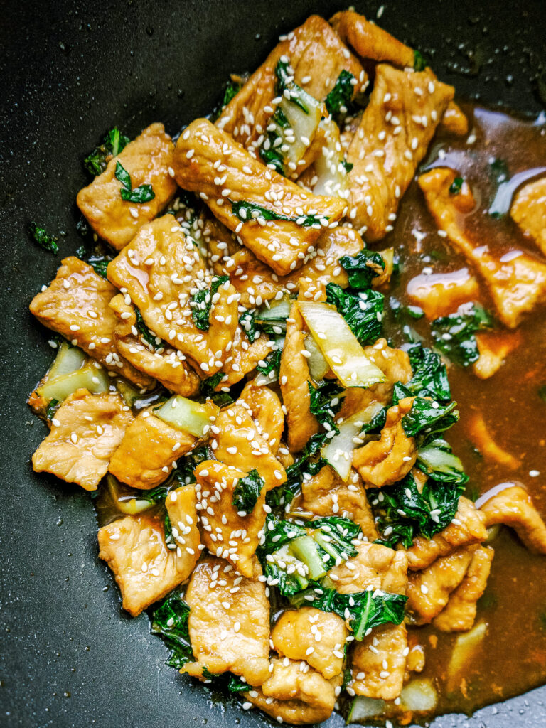 Teriyaki pork chops in a wok with bok choy and sesame seeds